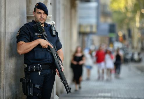 An armed police officer stands on a street in Las Ramblas, Barcelona, Spain, Friday (AP Photo/Manu Fernandez)