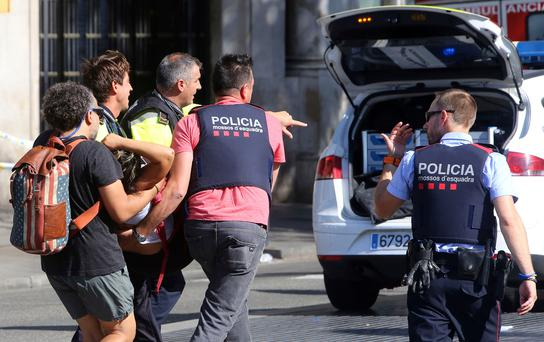 An injured person is carried in Barcelona, Spain, Thursday, Aug. 17, 2017, after a white van jumped the sidewalk in the historic Las Ramblas district, crashing into a summer crowd of residents and tourists and injuring several people, police said. (AP Photo/Oriol Duran)