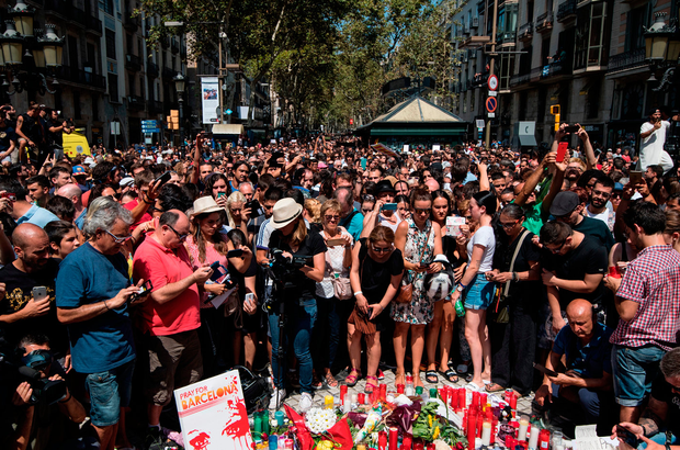 People gather around tributes laid on Las Ramblas yesterday after a minute's silence for the victims. Photo: Getty Images