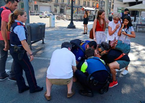 An injured woman is helped after the attack in the Las Ramblas district of Barcelona, Spain on Thursday. Picture: AP