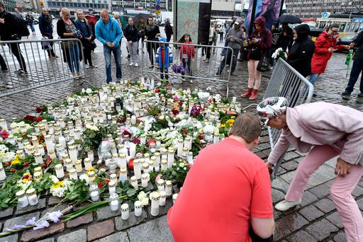 People bring memorial candles and flowers to the Turku Market Square for the victims of Friday's stabbings in Turku, Finland