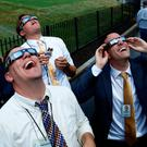 The sun in the eclipse was watched by members of the media at the White House Photo: Reuters