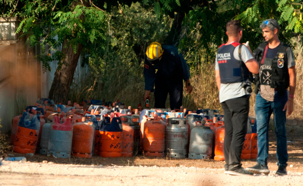 Firefighters carry gas canisters at the explosion site where the attacks of Barcelona were planned, in Alcanar, Tarragona province, Spain. Photo: AP