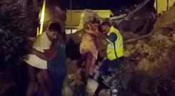 A woman is helped out of debris and rubble after an earthquake hit the island of Ischia, off the coast of Naples, Italy August 21, 2017 in this still image taken from video. Photo: REUTERS/Vincenzo Precisano