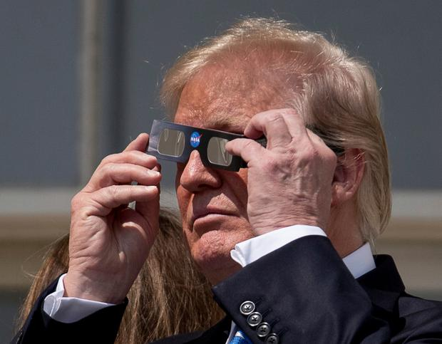 President Donald Trump puts on protective glasses to view the solar eclipse at the White House, Monday, Aug. 21, 2017, in Washington. (AP Photo/Andrew Harnik)