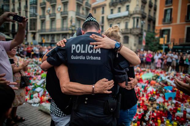 A policeman hugs to a boy and his family that he helped during the terrorist attack, at a memorial to the victims on Las Ramblas, Barcelona, Spain, Monday Aug. 21, 2017. (AP Photo/Santi Palacios)
