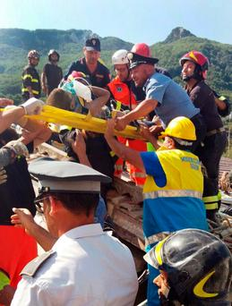 Firefighters and rescuers pull out a boy, Mattias, from the collapsed building in Casamicciola, on the island of Ischia, near Naples, Italy, a day after a 4.0-magnitude quake hit the Italian resort island, Tuesday, Aug. 22, 2017. irefighters freed a 7-month-old baby and an older brother from rubble of a house some seven hours after the quake, and are continuing work on rescuing another brother who remained trapped. (Italian Carabinieri, HO/ANSA via AP)