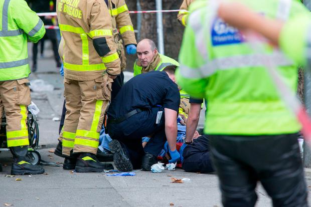 Paramedics work on one of the victims at the scene. Photo: Colin O'Riordan
