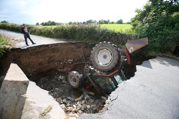 A man looks at a tractor which has fallen into a river after a road collapsed in Iskaheen, County Donegal after heavy rain left a trail of destruction. Photo: Niall Carson/PA Wire