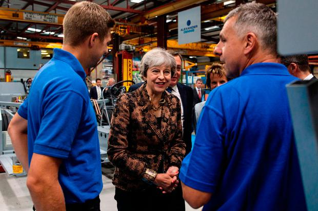 British Prime Minister Theresa May tours the Alexander Dennis bus and coach manufacturers factory in Guildford, Surrey, yesterday. Photo: Jack Taylor/PA