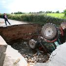 A man looks at a tractor which has fallen into a hole after a road collapsed in Iskaheen. Photo: Niall Carson/PA Wire