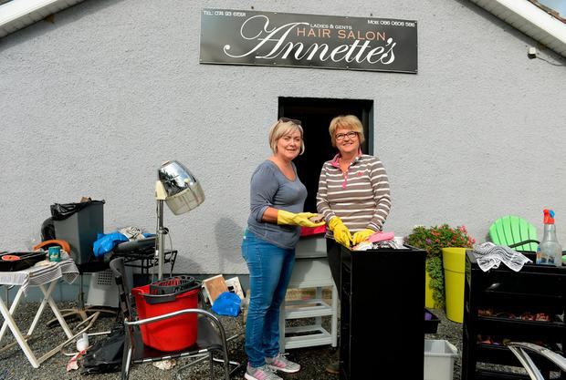 Annette's Hair Salon owner Annette Doherty (right) and friend Tina McDaid cleaning up after the floods. Photo: Caroline Quinn