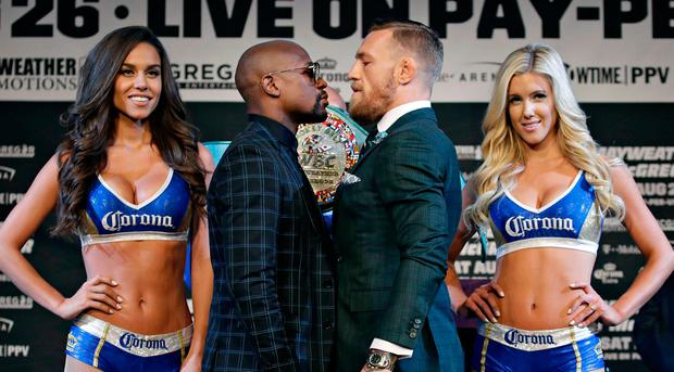 Floyd Mayweather Jr., center left, and Conor McGregor pose for photographers during a news conference (AP Photo/John Locher)