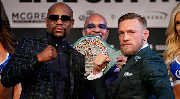 Floyd Mayweather Jr., left, and Conor McGregor pose for photographers during a news conference (AP Photo/John Locher)