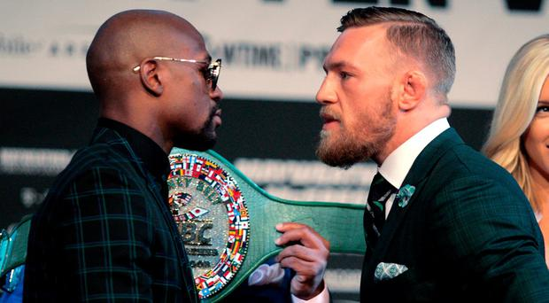 Boxer Floyd Mayweather Jr. (L) and MMA figher Conor Mcgregor face-off during a media press conference