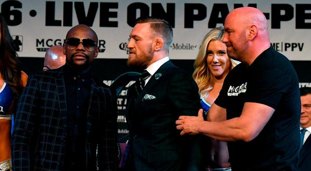 Boxer Floyd Mayweather Jr. poses as UFC lightweight champion Conor McGregor is pulled back by UFC President Dana White during a news conference at the KA Theatre at MGM Grand Hotel & Casino