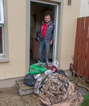 Father-of-three Liam Hegarty outside his home with some of his ruined clothing after the flooding. Photo: North West Newspix