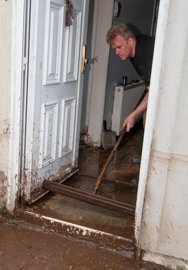 Darren Donaghey sweeping out water from his home in Burnfoot. Photo: North West Newspix