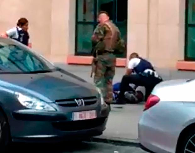This screengrab shows police officials and a soldier looking at a man on the pavement in the city centre of Brussels on August 25, 2017, where a man is alleged to have attacked soldiers with a knife and was shot./ AFP PHOTO / Belga / STR / Belgium OUTSTR/AFP/Getty Images