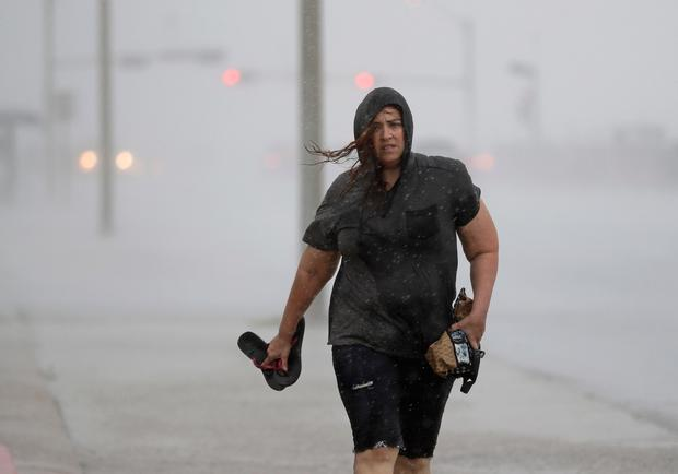 Hillary Lebeb walks along the seawall in Galveston, Texas as Hurricane Harvey intensifies in the Gulf of Mexico Friday, Aug. 25, 2017. Harvey is forecast to be a major hurricane when it makes landfall along the middle Texas coastline. (AP Photo/David J. Phillip)