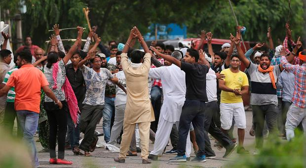 Supporters, back toward camera, try to calm other supporters of the Dera Sacha Sauda sect near an Indian court in Panchkula, India. (AP Photo/Altaf Qadri)