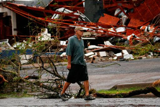 A man walks past a business which was left damaged after Hurricane Harvey hit Rockport, Texas, U.S. August 26, 2017. REUTERS/Adrees Latif