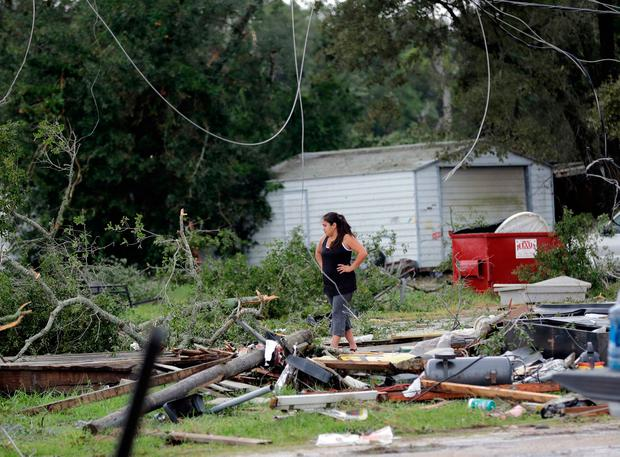 Jennifer Bryant looks over the debris where her family business once stood in the aftermath of Hurricane Harvey Saturday, Aug. 26, 2017, in Katy, Texas. Harvey rolled over the Texas Gulf Coast on Saturday, smashing homes and businesses and lashing the shore with wind and rain so intense that drivers were forced off the road because they could not see in front of them. (AP Photo/David J. Phillip)