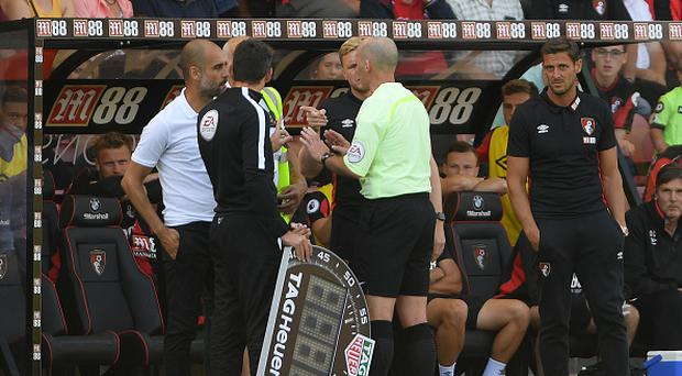 Referee Mike Dean talks to both Pep Guardiola and Eddie Howe during the Premier League match between AFC Bournemouth and Manchester City at Vitality Stadium on August 26, 2017 in Bournemouth, England. (Photo by Mike Hewitt/Getty Images)