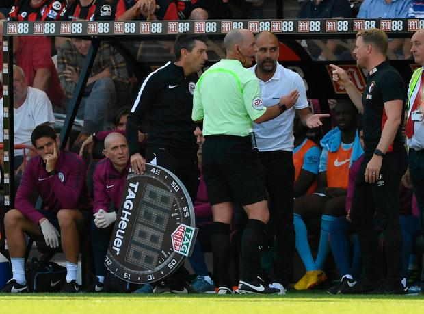 Manchester City manager Pep Guardiola and Bournemouth manager Eddie Howe with the referee after Raheem Sterling was sent off Photo: REUTERS/Tony O'Brien