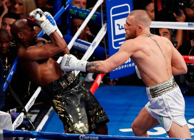 Conor McGregor hits Floyd Mayweather Jr. in a super welterweight boxing match Saturday, Aug. 26, 2017, in Las Vegas. (AP Photo/Eric Jamison)