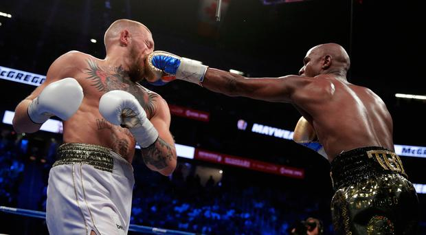 Floyd Mayweather Jr. jabs Conor McGregor in a super welterweight boxing match Saturday, Aug. 26, 2017, in Las Vegas. (AP Photo/Isaac Brekken)