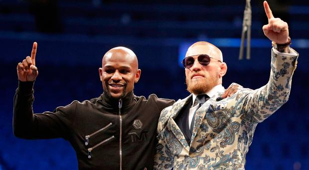 Floyd Mayweather Jr. and Conor McGregor pose during a news conference after a super welterweight boxing match Sunday, Aug. 27, 2017, in Las Vegas. (AP Photo/Isaac Brekken)