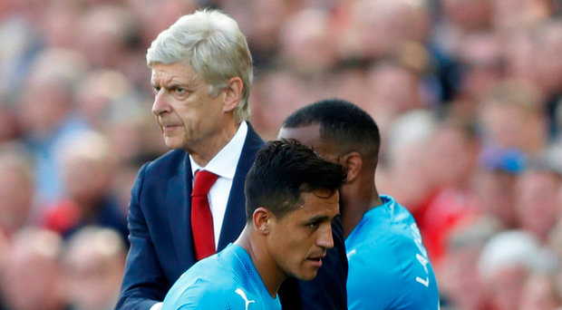 Alexis Sanchez cuts a sorry figure as he walks past Arsene Wenger after being substituted. Photo: Carl Recine/Reuters