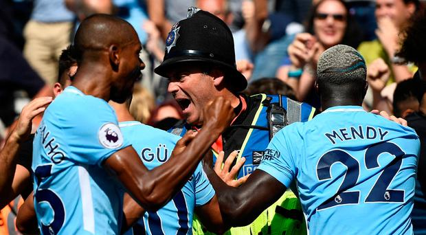 Manchester City's Sergio Aguero and Benjamin Mendy with Police after Raheem Sterling celebrates scoring their second goal. Photo: Dylan Martinez/Reuters
