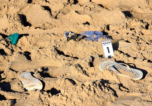 A pair of beach slippers lie on the sand where a suspected gang rape of a Polish tourist and the beating of her partner took place in Rimini, Italy, Saturday, Aug. 26, 2017. (Manuel Migliorini/ANSA via AP)