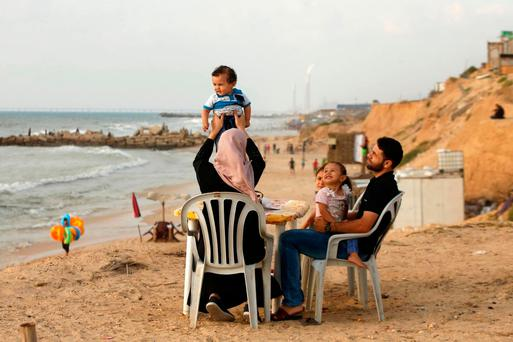 A woman lifts up her son as she sits with her family on a beach in Beit Lahiya town in the northern Gaza Strip on 6 July 2017 REUTERS