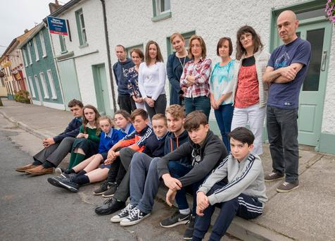 Front from left, students Rory Howley, Ciara Walsh, Abi Frisby, Sadhbh McDonnell, Killian Dungan, Darragh Davis, Chris O'Keeffe, Cian McCormack and Evian McCormack pictured with their disgruntled parents (back row) where the school bus to New Ross used to stop in Mullinavat, Co Kilkenny. Photo: Dylan Vaughan