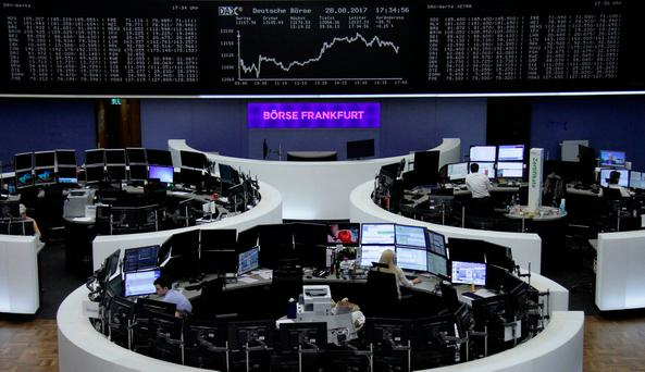 Traders work in front of the German share price index, DAX board, at the stock exchange in Frankfurt