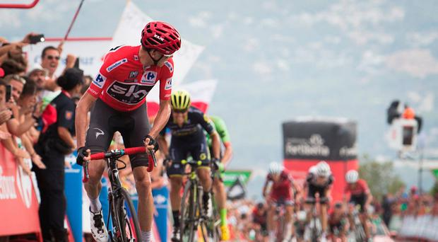 Sky's British cyclist Chris Froome looks back as he crosses the finish line to win the 9th stage of the 72nd edition of