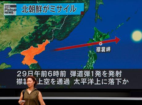 A woman walks past a large TV screen showing news about North Korea's missile launch in Tokyo, Japan, August 29, 2017. REUTERS/Kim Kyung-Hoon