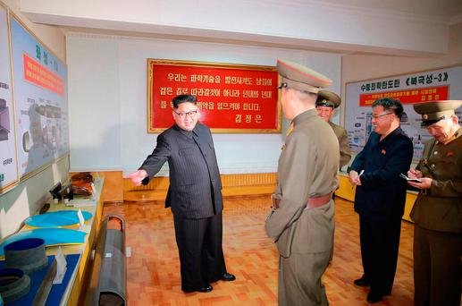 In this undated photo distributed Wednesday, Aug. 23, 2017, by the North Korean government, leader Kim Jong Un, left, visits the Chemical Material Institute of Academy of Defense Science at an undisclosed location in North Korea. North Korea's state media released photos that appear to show concept diagrams of the missiles hanging on a wall behind leader Kim Jong Un, one showing a diagram for a missile called
