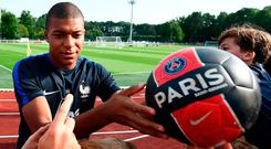 Kylian Mbappe signs autographs before a training session in Clairefontaine en Yvelines. Photo: AFP/Getty Images