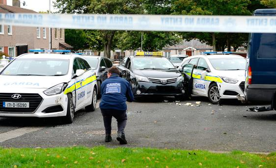 A garda examines the scene of the incident where the hijacked taxi was stopped by gardaí in Finglas, Dublin, yesterday. Photo: Caroline Quinn