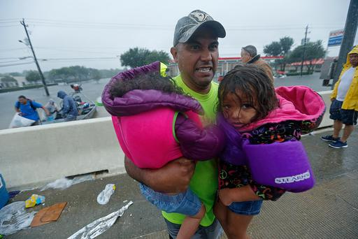 A man carries children after being rescued by members of the Louisiana Department of Wildlife and Fisheries and the the Houston Fire Department after residents were stranded by floodwaters due to Tropical Storm Harvey, Monday, Aug. 28, 2017. (AP Photo/Gerald Herbert)