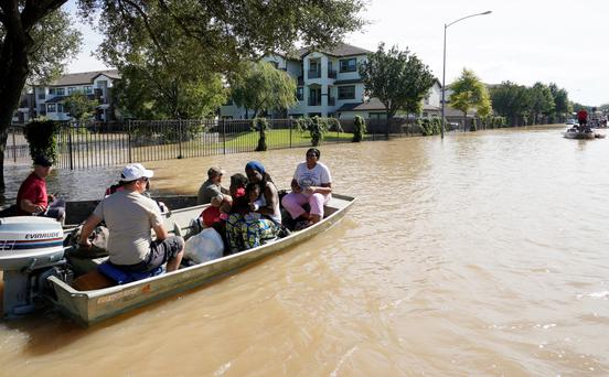 A family is evacuated by boat from Tropical Storm Harvey floodwaters in western Houston, Texas August 30, 2017. REUTERS/Rick Wilking