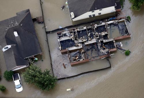 A burned out home is surrounded by floodwaters from Tropical Storm Harvey Tuesday, Aug. 29, 2017, in Spring, Texas. (AP Photo/David J. Phillip)