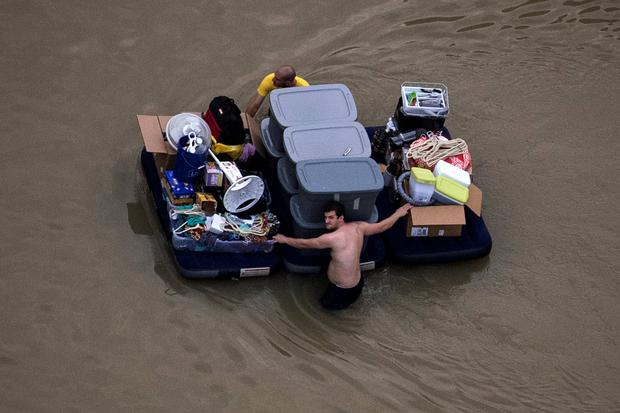 Residents wade with their belongings through flood waters brought by Tropical Storm Harvey in Northwest Houston, Texas, U.S. August 30, 2017. Picture taken August 30, 2017. REUTERS/Adrees Latif