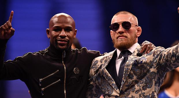 Floyd Mayweather Jr. and Conor McGregor pose for pictures during a news conference after Mayweather's 10th-round TKO victory in their super welterweight boxing match on August 26, 2017 at T-Mobile Arena in Las Vegas, Nevada. (Photo by Jeff Bottari/Zuffa LLC/Zuffa LLC via Getty Images)