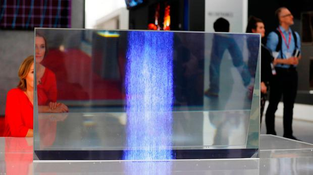 A woman sits behind a transparent OLED tv from Panasonic at the IFA Electronics show in Berlin, Germany August 31, 2017. REUTERS/Hannibal Hanschke