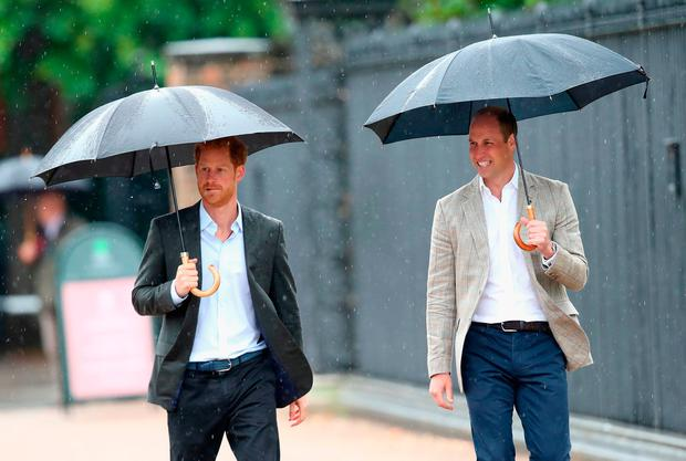 Prince William, Duke of Cambridge and Prince Harry look upon flowers, photos and other souvenirs left as a tribute to Princess Diana near The Sunken Garden at Kensington Palace on August 30, 2017 in London, England